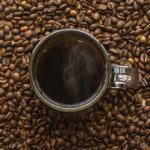 Overhead of coffee in mug surrounded by coffee beans